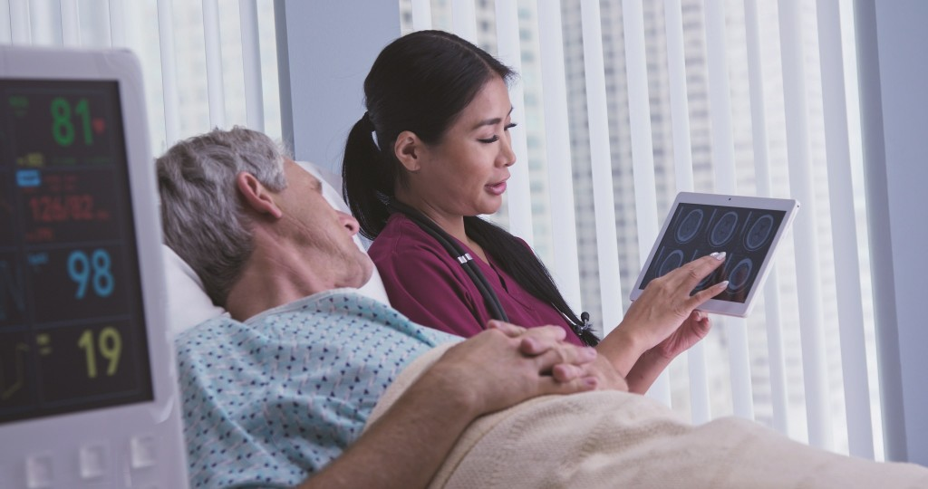 Doctor Sharing Test Results On Tablet Computer With Patient In Hospital Bed